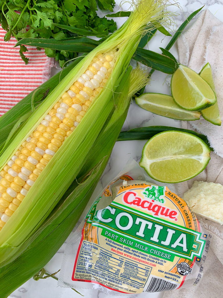 shucked ear of corn, fresh cilantro, lime wedges, and cotija cheese