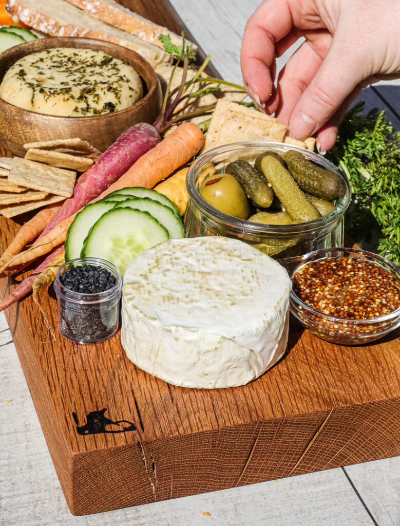 hand reaching to grab a cracker from a cheese board that has carrots, mustard, salt, and vegan cheese.