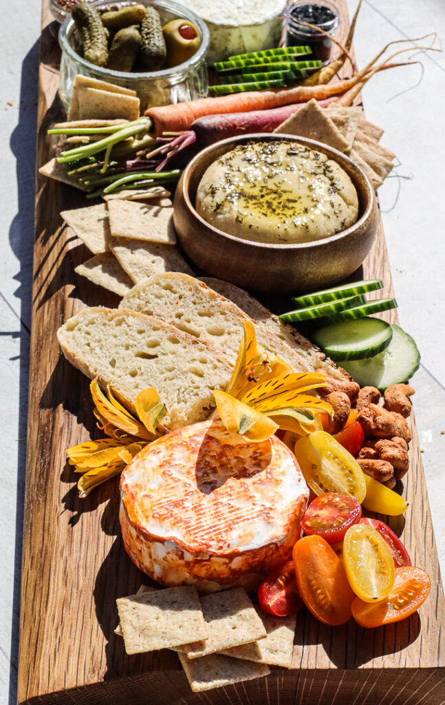 long wooden cheese board with orange colored cheese (paprika), bread, carrots, cucumbers, tomatoes.