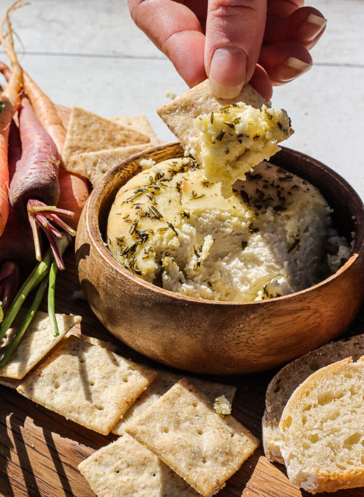 hand dipping a cracker into soft, herb topped cheese.
